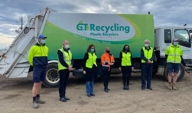 five persons wearing masks standing beside a recycling truck